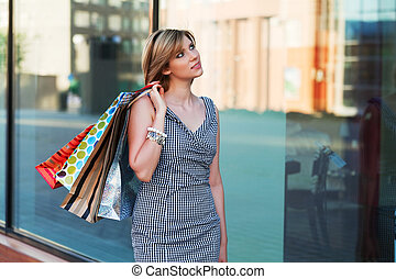 Young woman with shopping bags against a store window