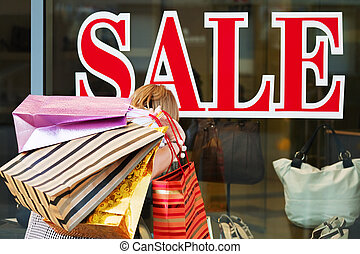 Window shopping - Young woman with shopping bags against a...