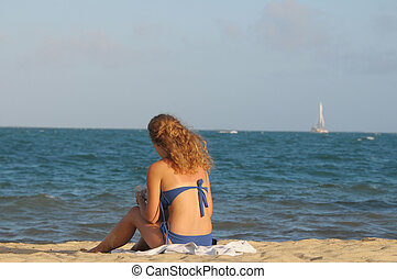 Girl on the beach - Young girl sitting on the beach in...