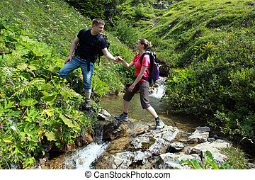 Couple hiking in mountains - A young male hiker is helping a...