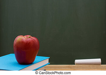 School Days - Book with an apple in front of a chalkboard,...