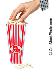 Hand grabbing popcorn out of container