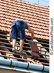 Worker on the roof - Man working in the roof of a building