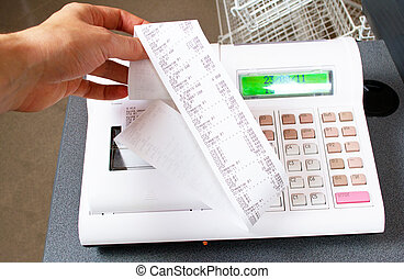 Close-up image of a shop-assistant's hand pressing a key of an electronic cash register in a shop.