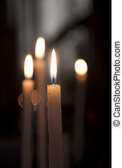Candles glowing in the church. Shallow depth of field.