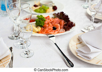 Plates with cold snack on table