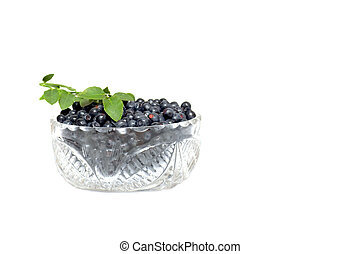 Bowl full whortleberries and green leaves on a white. -...