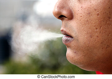 Man exhaling smoke - A young caucasian man exhaling...