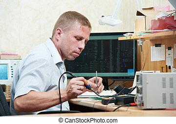 worker soldering microchip scheme - mechanical technician...