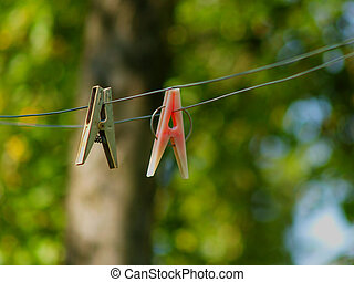 Clothes-peg - Old clothes-peg on wire. Green trees...