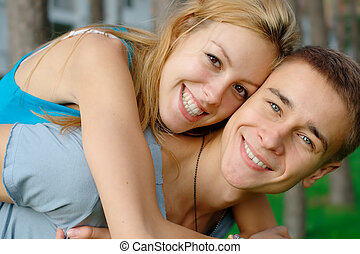 Happy teen couple outdoors - Close-up portrait of a happy...