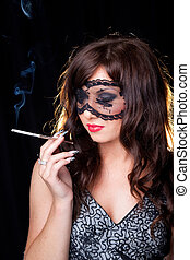 portrait of attractive young brunette girl with long dark ringlets and fine art manicure wearing lacy mask on her eyes holding graceful silver mouthpiece and smoking thin ladies' cigaret on black bac