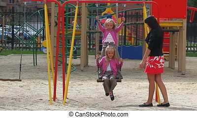 Amusing in park - Mother pushing her daughters on swings