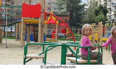 Merry-go-round - Little girl turning her sister on carousel...