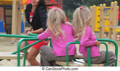 Woman with daughters - Woman turning carousel with her two...
