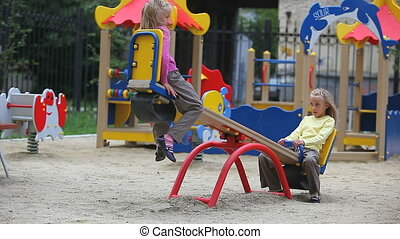 Twins on swings - Two little sisters having fun on swings