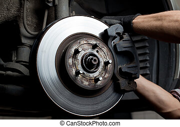 Car mechanic repair brake pads - Closeup of car mechanic...