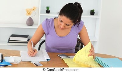 Brunette Woman doing her accounts in the living room