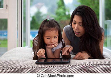 Digital Tablet Lifestyle - Mother and daughter laying on...