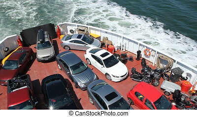 Car ferry - Pan across vehicles and tilt up to wake and...