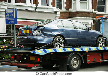 Crashed car, after traffic accident, being towed by a tow...