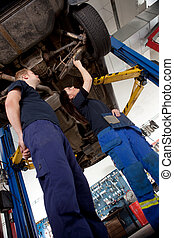 Two Mechanics Looking at Car - A Man and Woman mechanic...