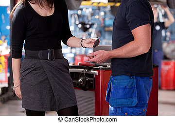 Customer in mechanic Shop Delivering Key - A customer in a...
