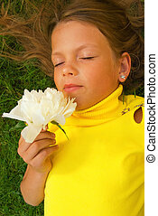 Little girl with a white flower lying on a green grass