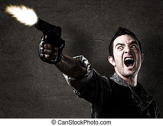man shooting a gun against a eroded wall