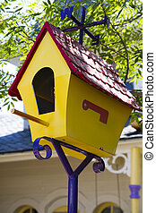cartoonish yellow birdhouse with red roof and
