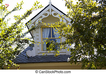 beautiful country house attic window with white courtains...