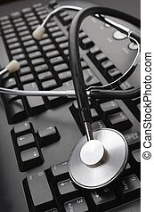 online - close up of a stethoscope and a computer keyboard