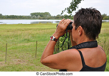 Senior woman watching birds in a lake