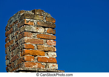 Old brick chimney and blue sky background