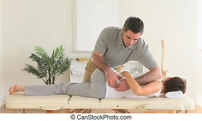 Chiropractor stretching the back of a woman in a room