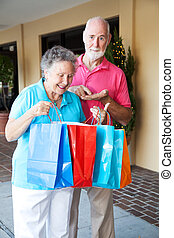 Shopping Seniors - Inflation - Senior couple shopping. She's...