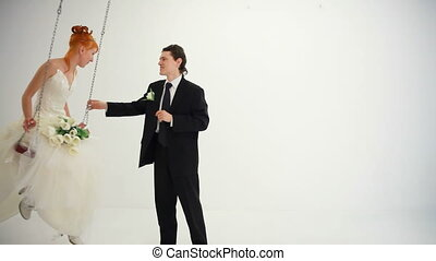 Bride rides on a swing