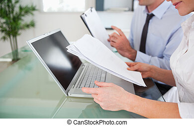 Managers typing a report from blueprint documents in an...