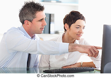 Man showing something to his coworker on a computer in an...