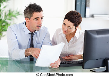 Office workers looking at a document in an office