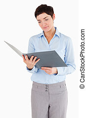 Portrait of a businesswoman looking at a binder against a...