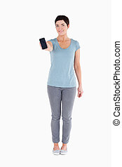 Smiling woman showing a smartphone against a white...