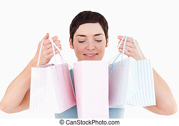 Woman looking in her shopping bags against a white...