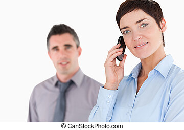 Woman telephoning while her colleague is posing