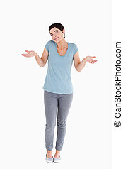 Clueless cute woman posing against a white background