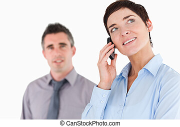 Woman making a phone call while her colleague is posing