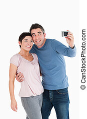 Portrait of a couple taking a picture of themselves against...