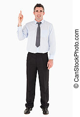 Businessman pointing at copy space against a white...