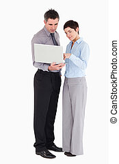 Office workers using a laptop against a white background
