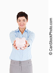 Serious woman holding a piggy bank